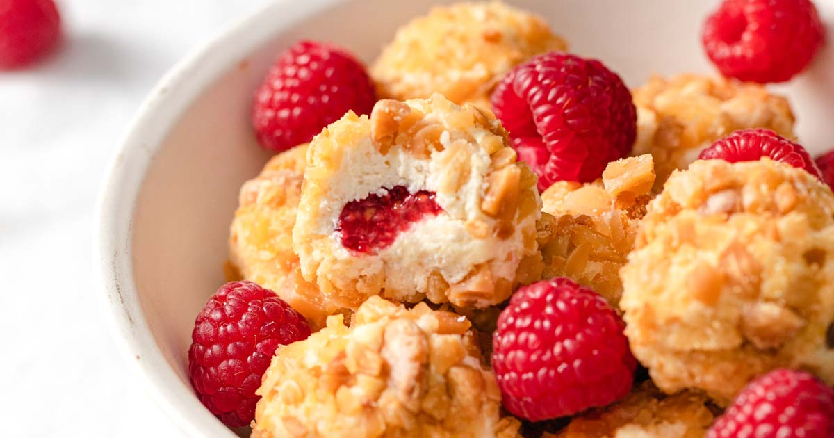 raspberry cheesecake bites rolled in roasted chopped almonds in a bowl