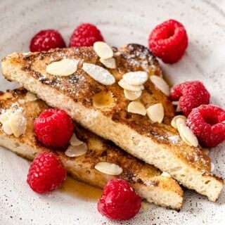 french toast slices on a plate with almonds and raspberries
