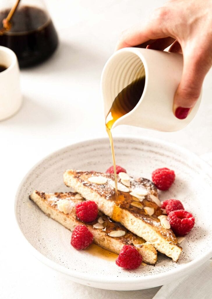 hand pouring sugar free syrup over french toast