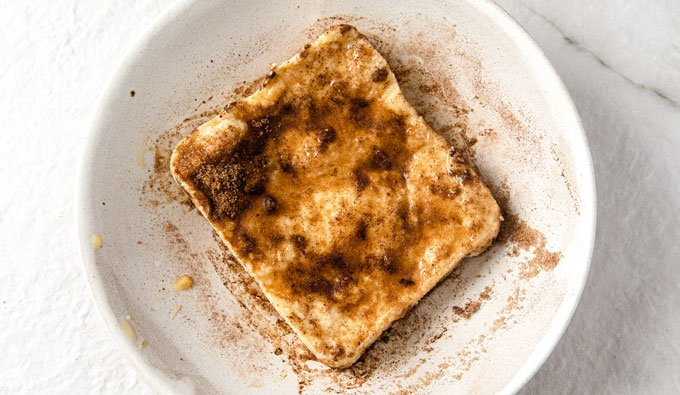 a slice of keto microwave bread on a plate with cinnamon and sweetener