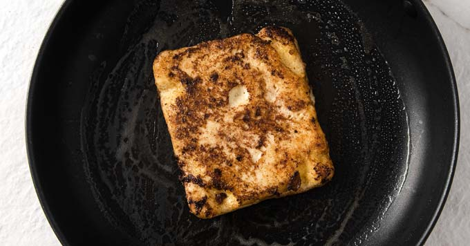 a slice of toast coated in egg and brown sweetener in a frying pan