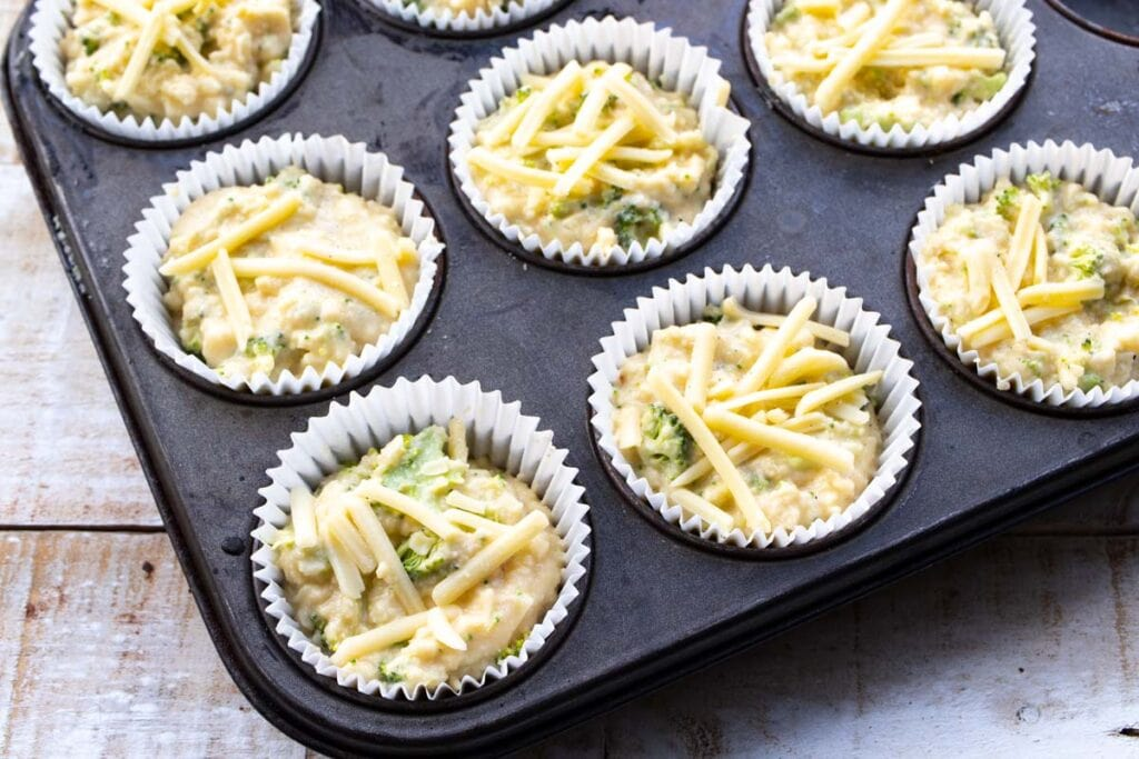 muffin batter topped with cheese in paper cups