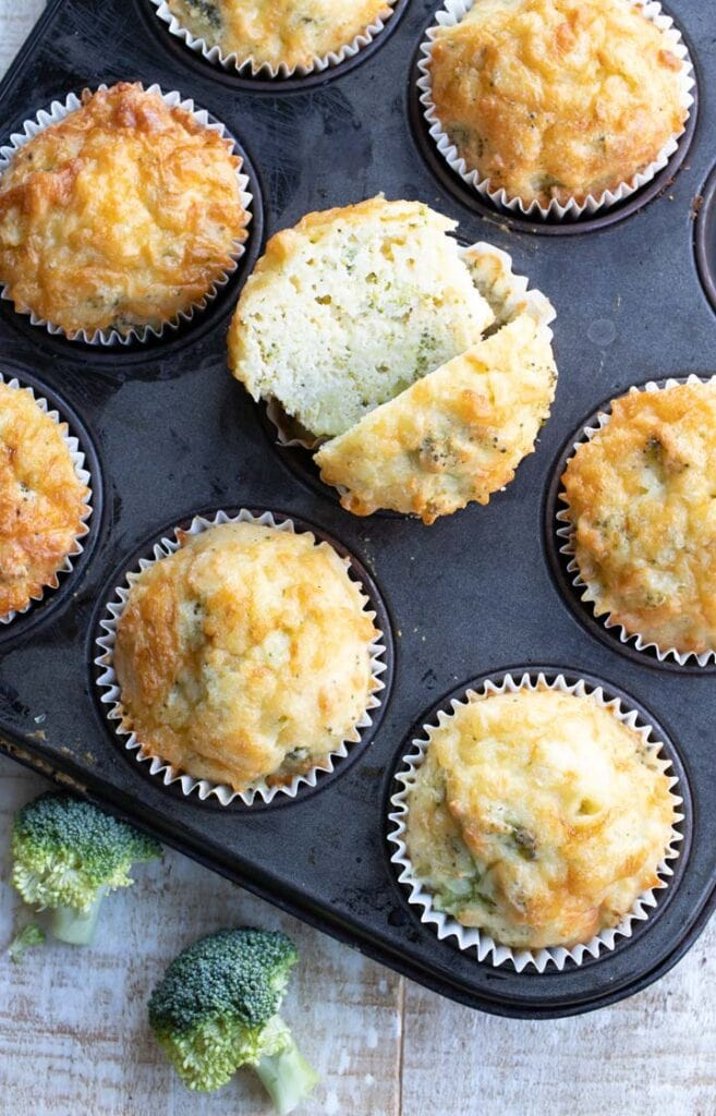 broccoli cheese muffins in a muffin tin , one is cut open showing the inside