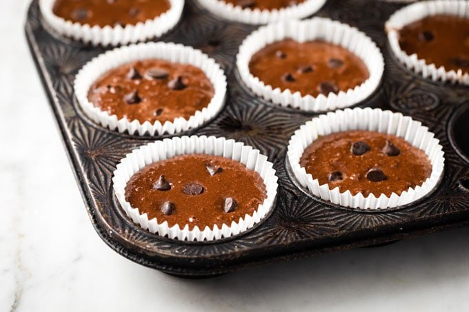 a muffin pan with unbaked chocolate muffins