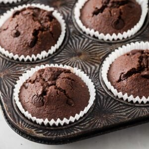 keto chocolate muffins in white paper cases in a metal baking pan