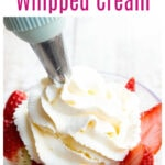 whipped cream on sliced strawberries in a bowl