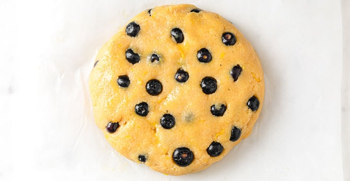 dough with blueberries shaped into a round disc
