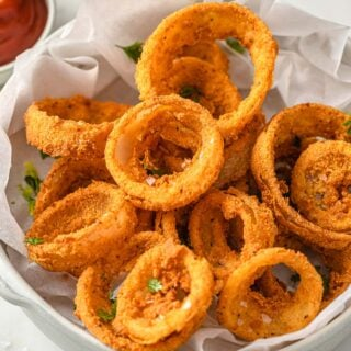 "keto onion rings with low carb ""breading"" in a bowl"
