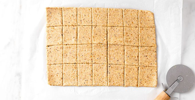 dough rolled out in a square and sliced into square crackers with a pizza cutter