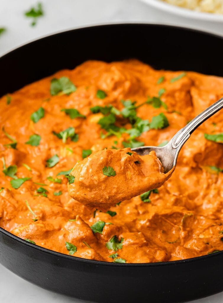 spoon lifting low carb chicken tikka masala out of a pan