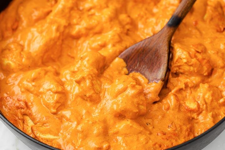 wooden spoon stirring chicken in masala sauce