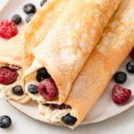 protein crepes on a plate, rolled up and filled with cream and berries