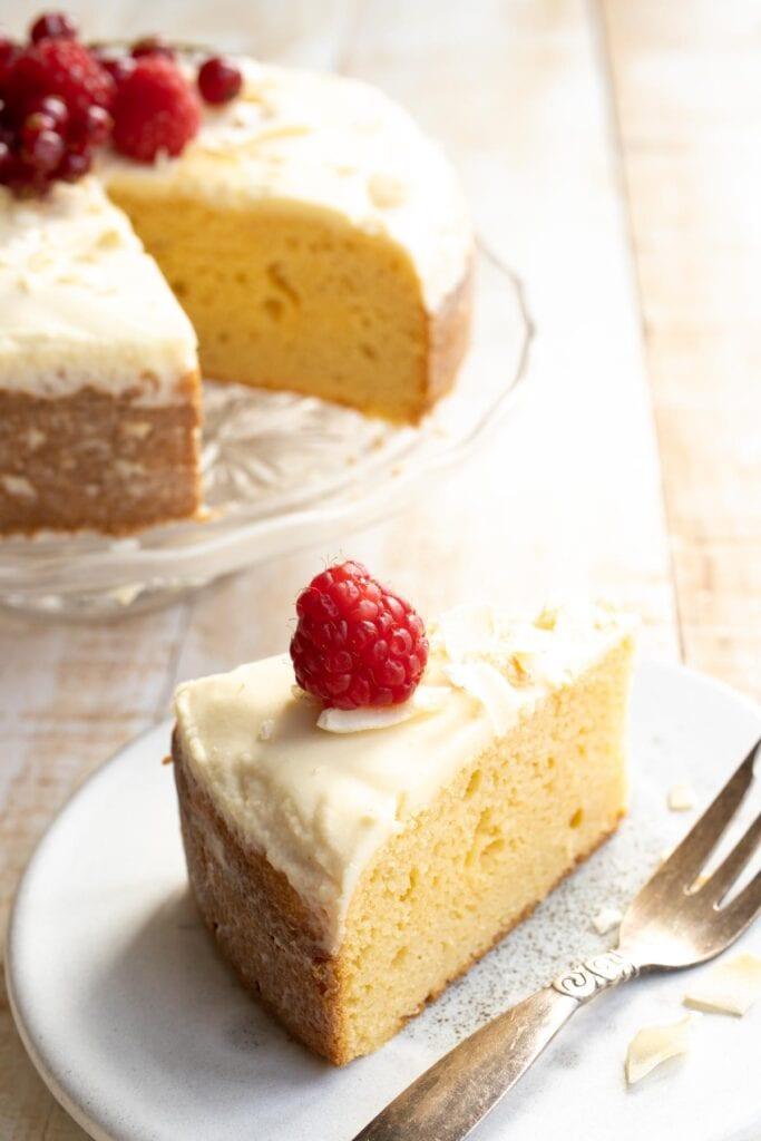 a slice of cake on a plate end a cake on a cake stand