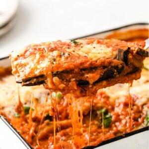 closeup of a spatula lifting a portion of keto eggplant parmesan from a casserole dish