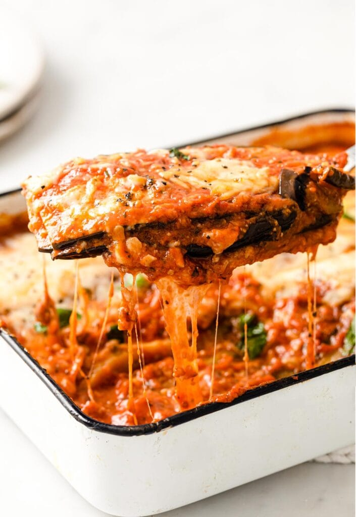 Spatula lifting a portion of baked aubergine parmigiana from a casserole dish