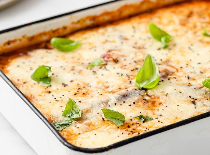 casserole dish with baked eggplant topped with melted cheese and basil leaves