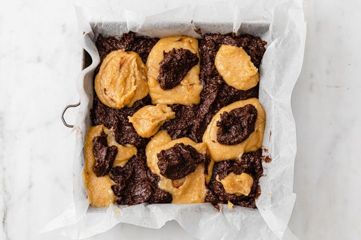 dollops of peanut butter batter and brownie batter in a square baking pan