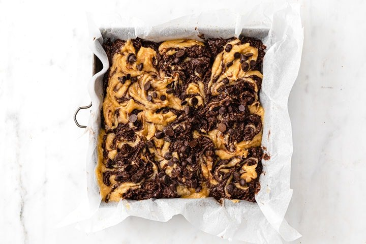 a baking pan with brownie and peanut butter batter swirled into each other, topped with sugar free chocolate chips