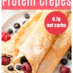 a plate with three rolled up protein crepes filled with cream and berries