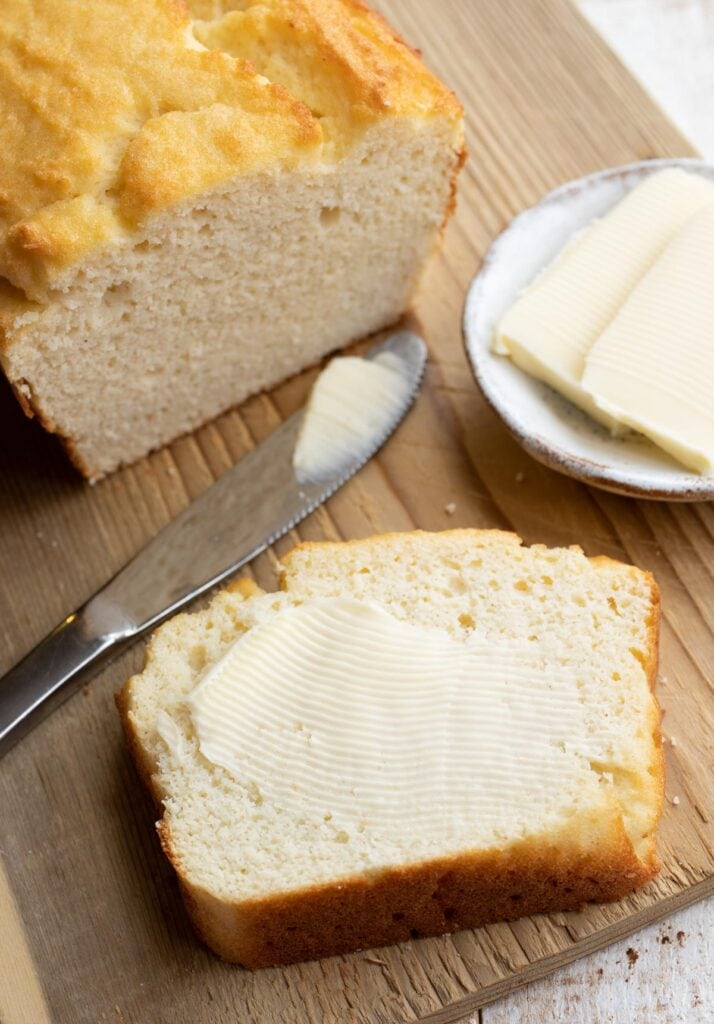 a slice of coconut flour bread spread with butter and a knife