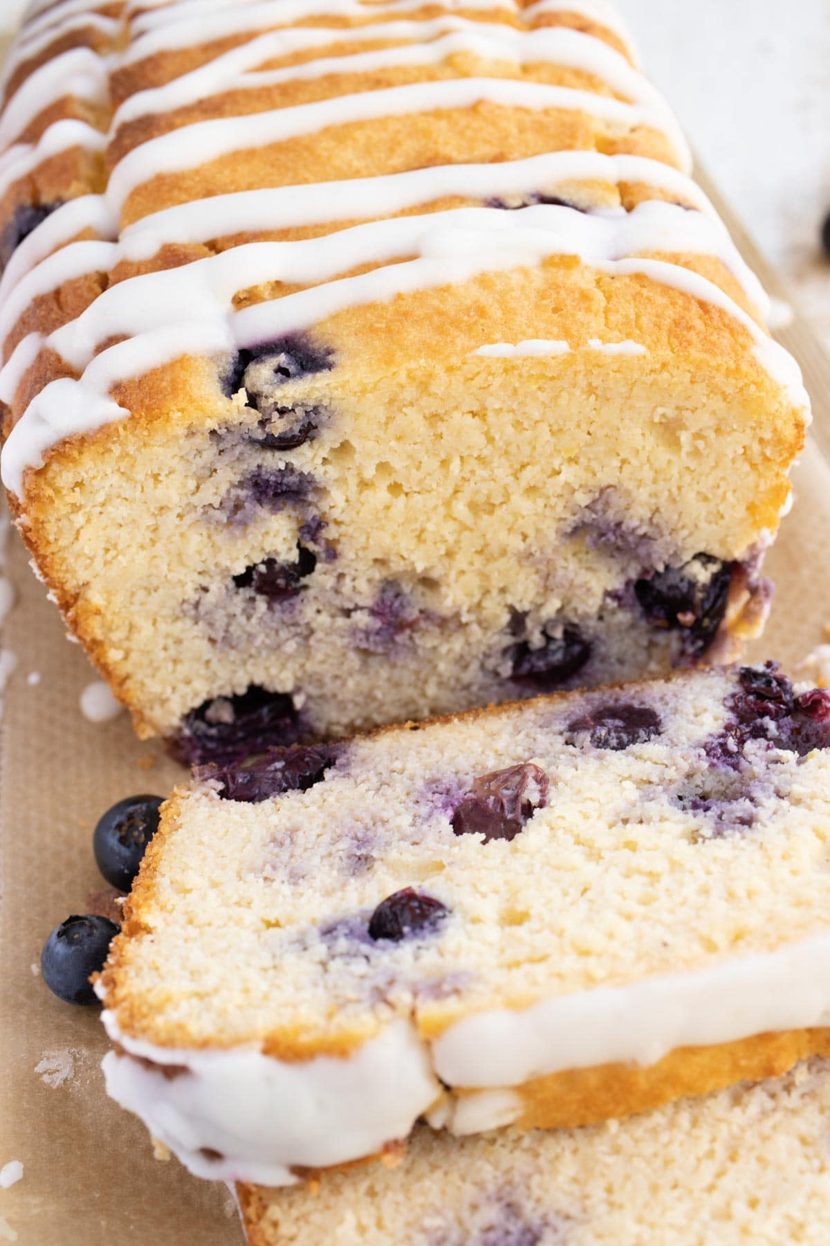keto blueberry bread topped with lemon icing sliced open