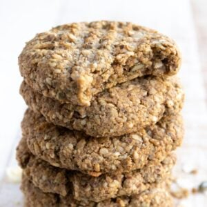 a stack of seeded keto breakfast cookies with a criss cross pattern on the tops, the top cookie has been bitten into