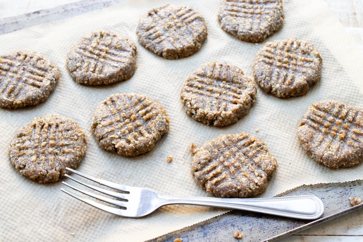 unbaked cookies on a cookie sheet lined with parchment paper and a fork