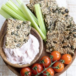a snack platter with keto seed crackers, vegetables and dips