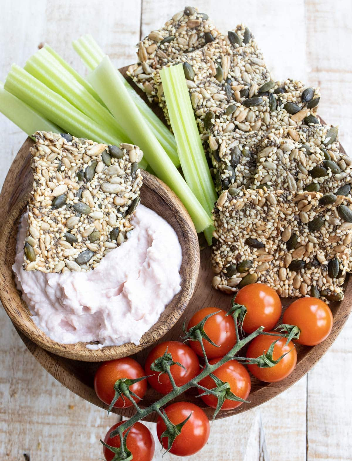keto seed crackers on a wooden board with taramasalata, celery sticks and cherry tomatoes