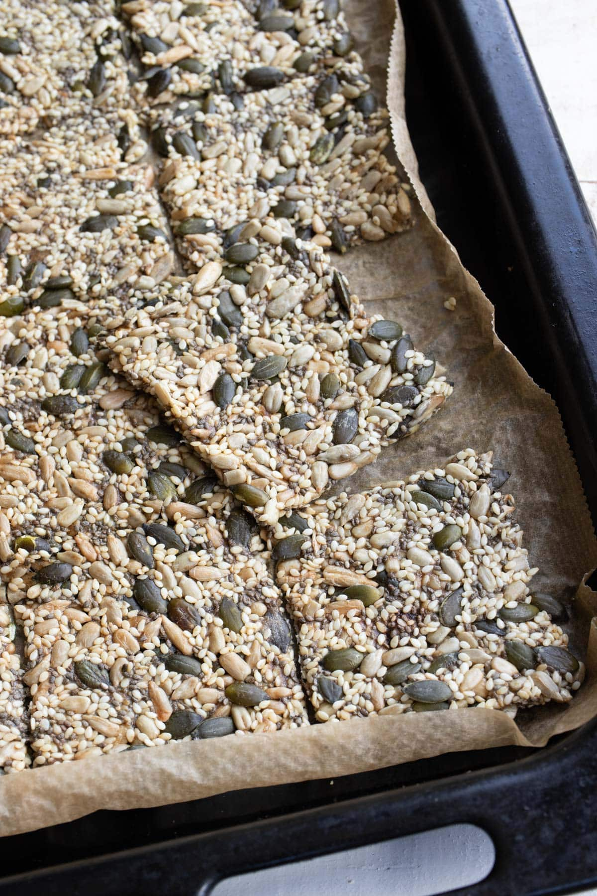freshly baked keto seed crackers on a baking pan lined with parchment paper