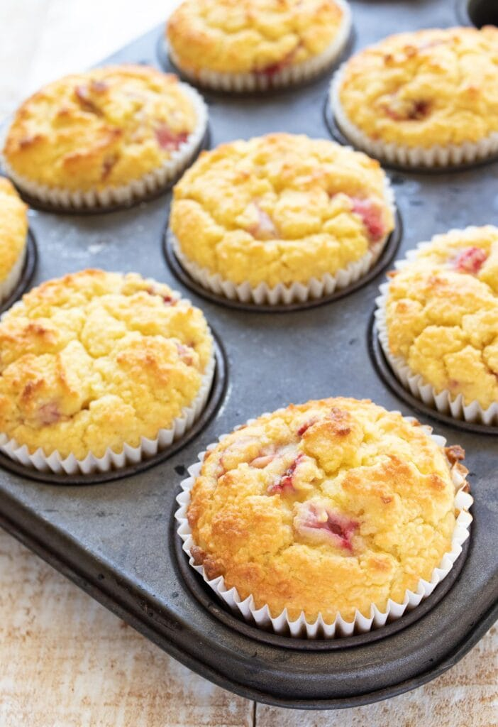 strawberry muffins in white paper cases in a muffin pan