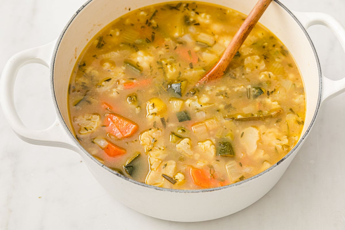 veggie soup in a saucepan and a wooden spoon
