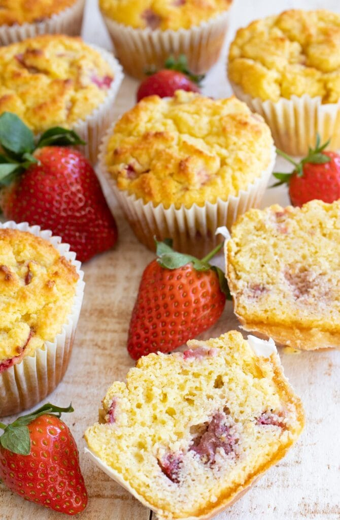 a halved strawberry muffin o a table showing the inside, surrounded by strawberries and more muffins in the background