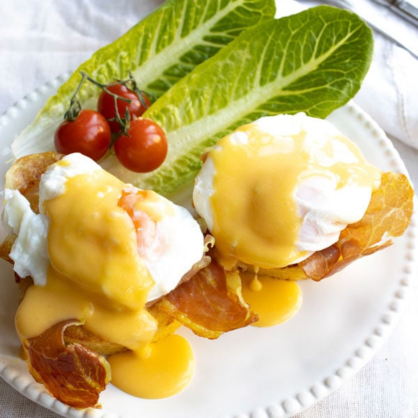 Eggs benedict with hollandaise sauce o a plate with salad garnish