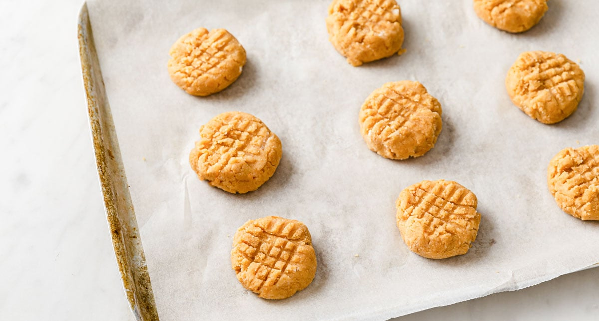 unbaked cookies on a baking tray lined with parchment paper
