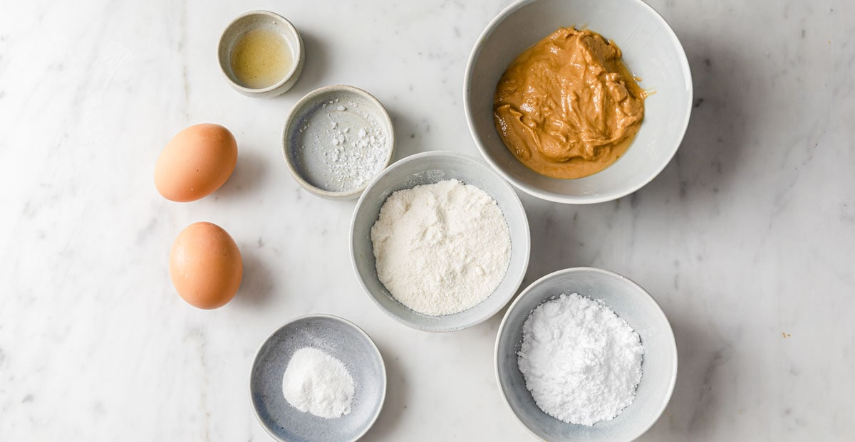ingredients for cookies - 2 eggs, peanut butter, coconut flour and more, all measured into bowls