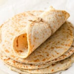 A rolled up coconut flour tortilla on a stack of tortillas