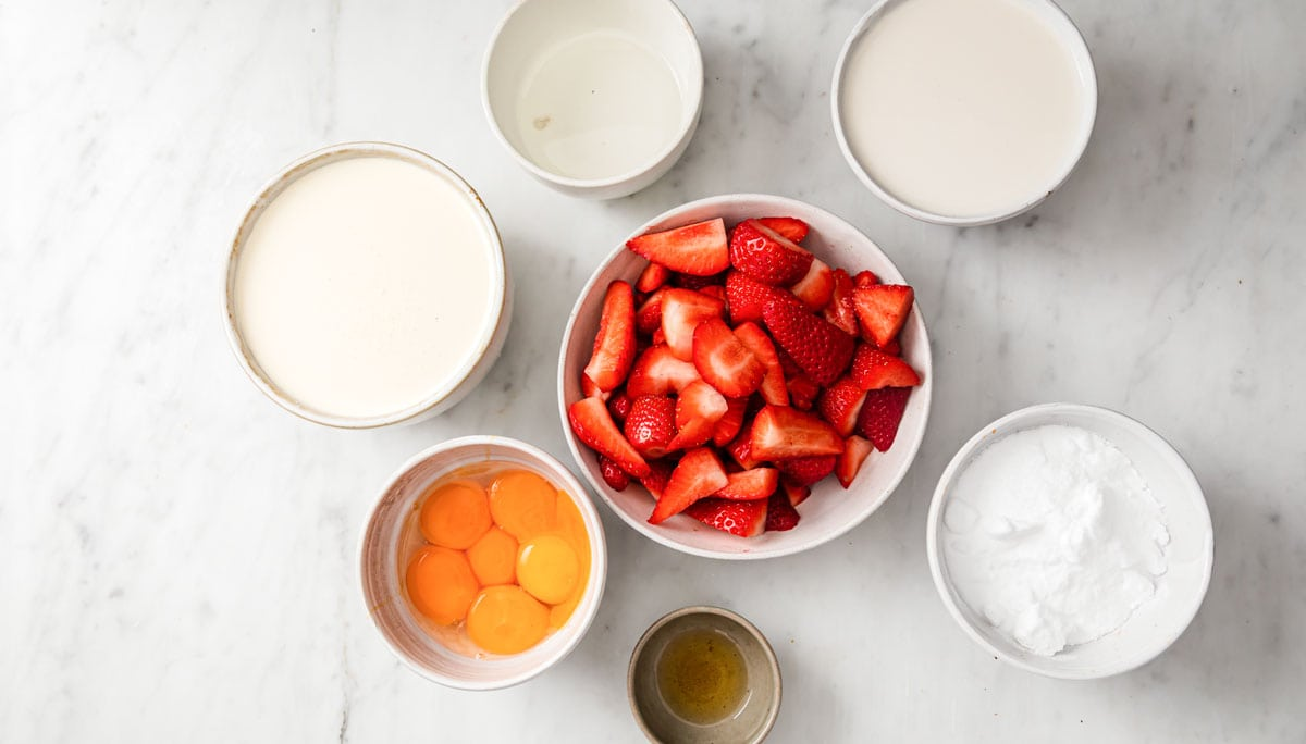 quartered strawberries and more ingredients measured into bowls