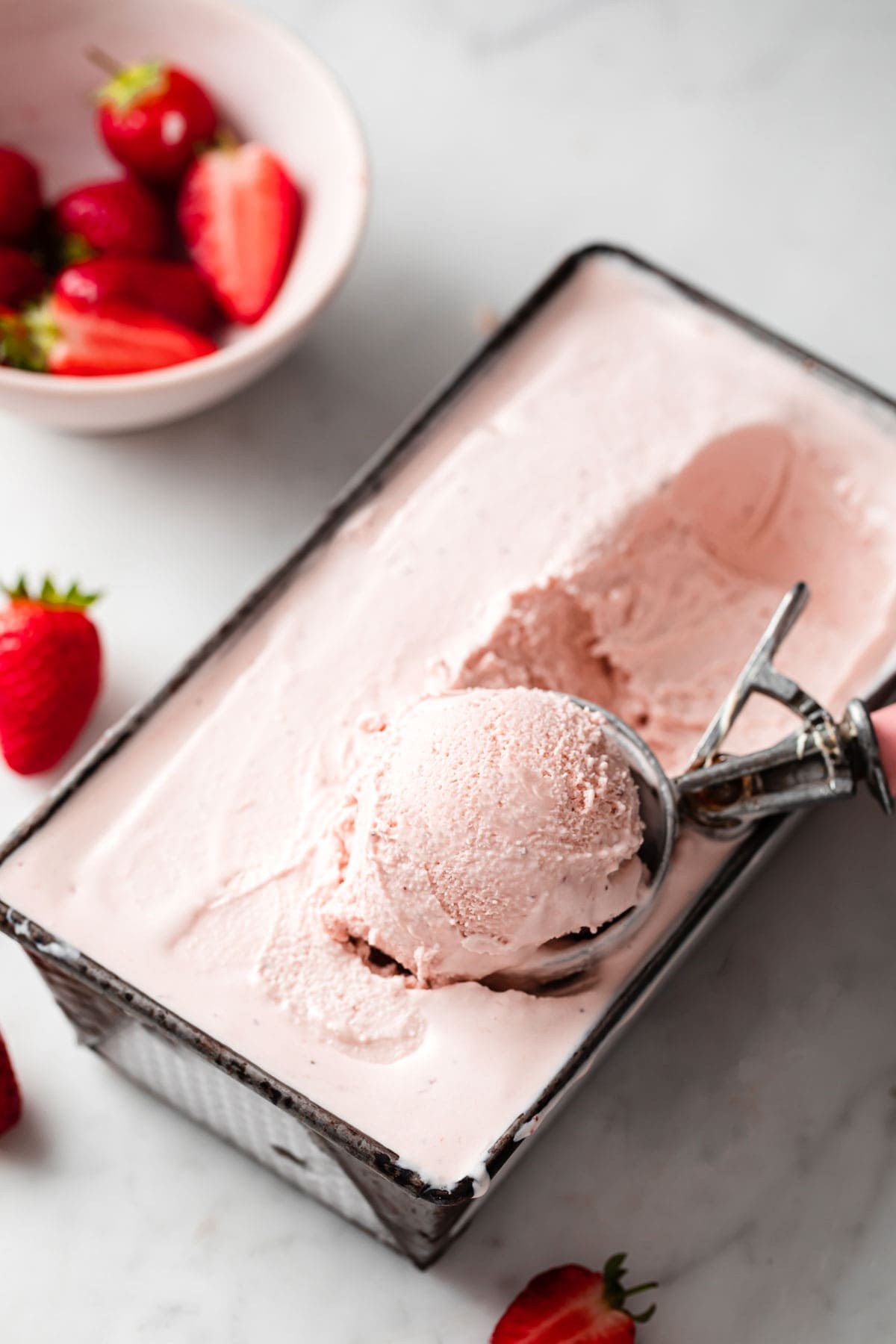 scooping low carb strawberry ice cream out of a container