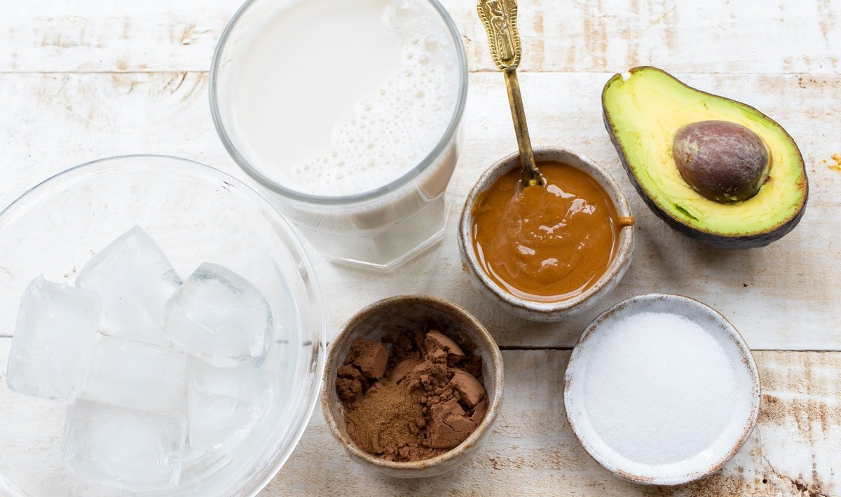 ingredients to make this recipe - avocado, peanut butter, cocoa, milk and sweetener