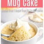 a keto vanlla mug cake in a white mug with a dollop of whipped cream