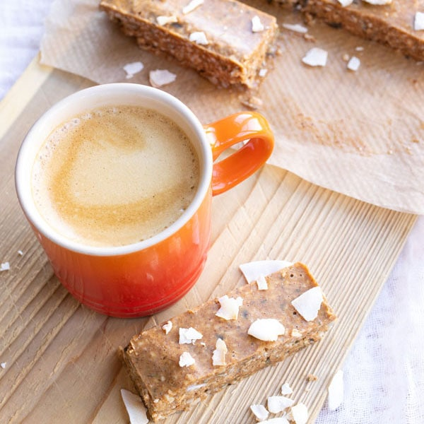 No bake breakfast bars on a wooden board with a cup of espresso
