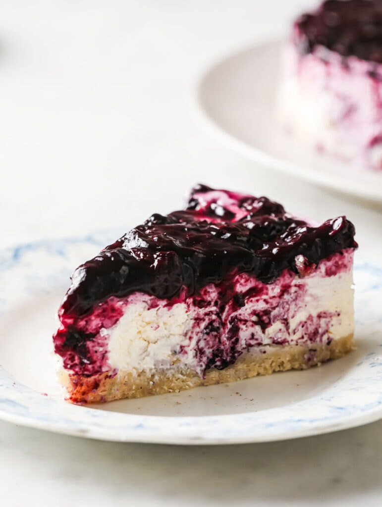 a slice of blueberry topped cheesecake on a plate