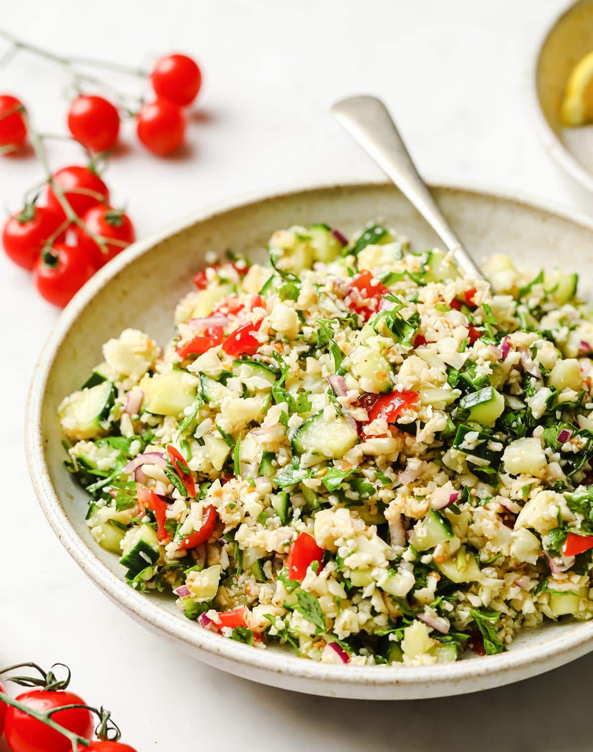 cauliflower tabbouleh in a bowl and tomatoes
