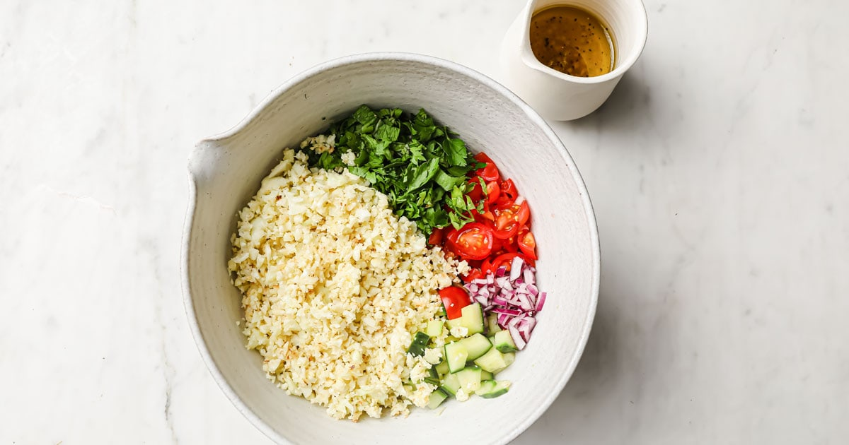 a bowl with cauliflower rice, chopped vegetables and dressing before mixing
