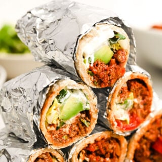 a stack of keto beef burritos packed in aluminium foil and sliced in half