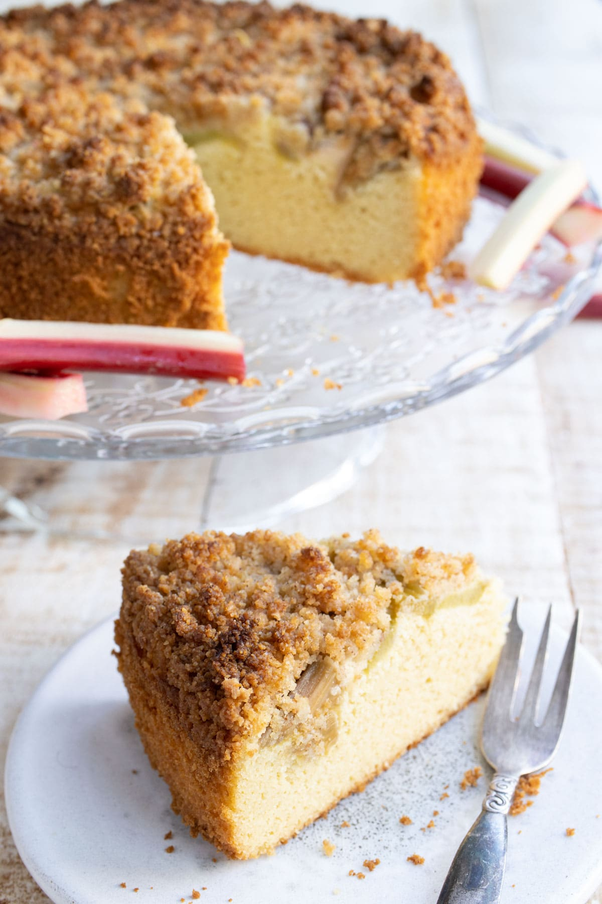 a slice of rhubarb cake with streusel on a plate with a fork and the cake on a cake stand