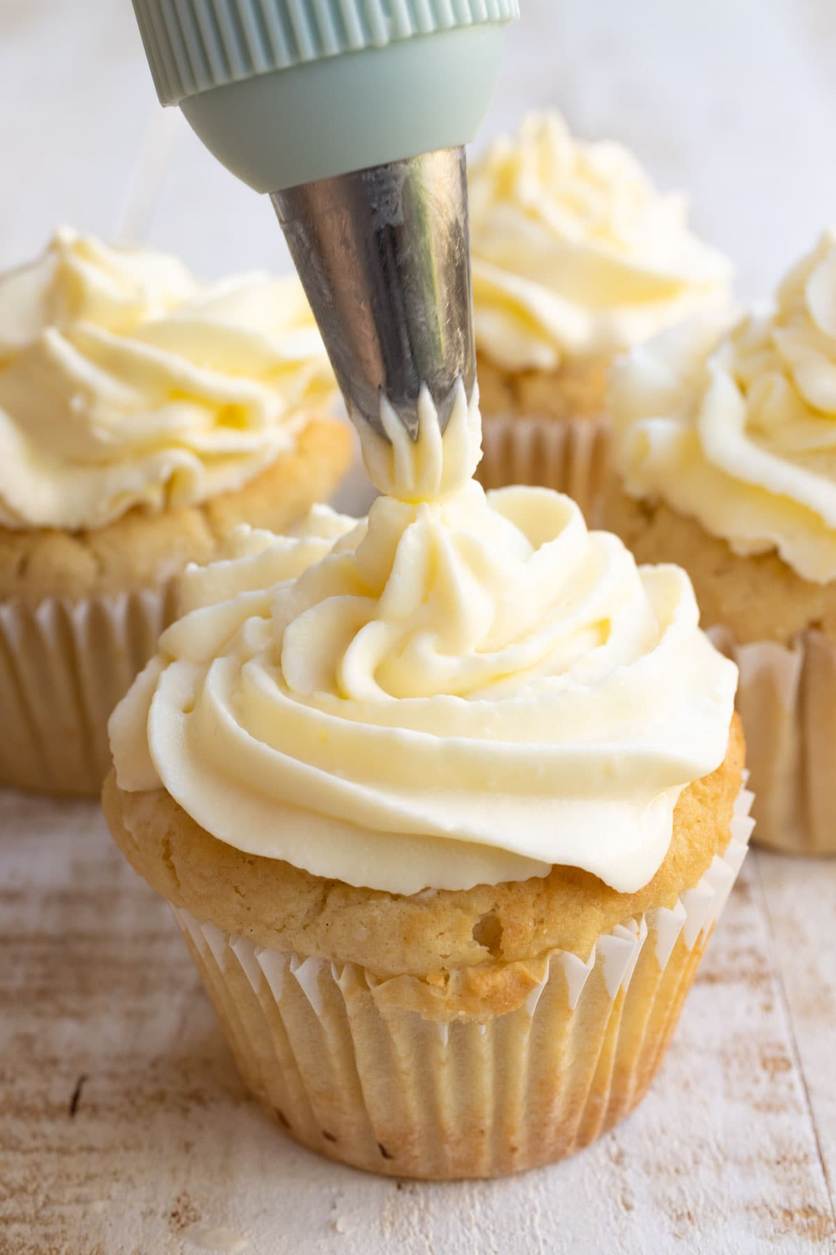 piping cream cheese frosting onto vanilla cupcakes