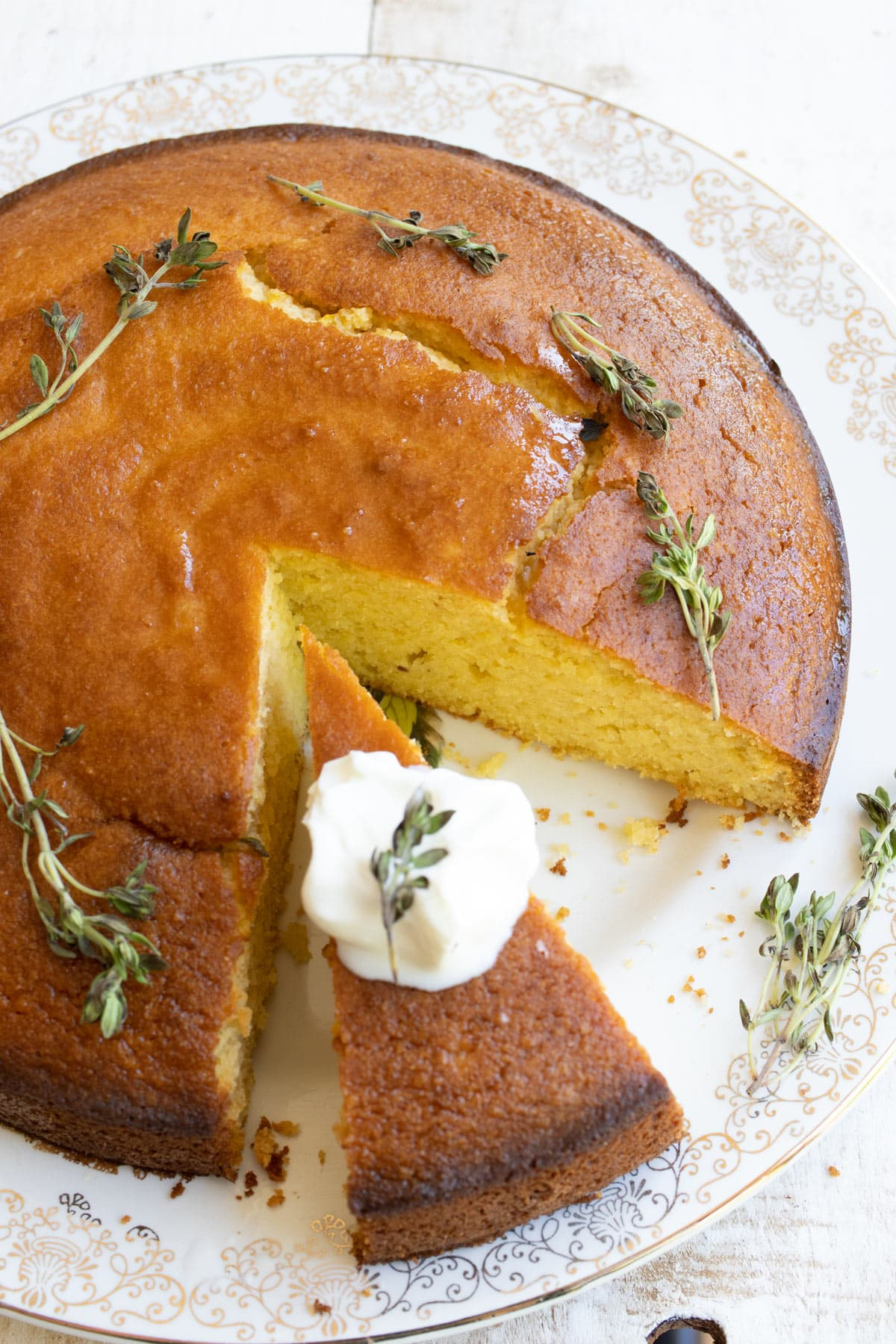 olive oil cake on a platter and scattered lemon thyme, one slice is topped with yoghurt