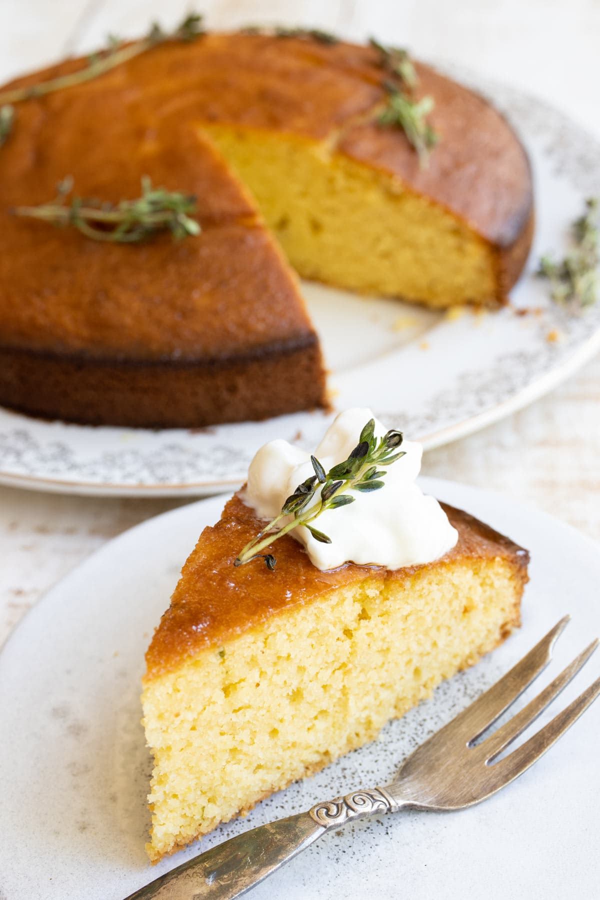 a slice of almond flour olive oil cake topped with greek yoghurt and lemon thyme